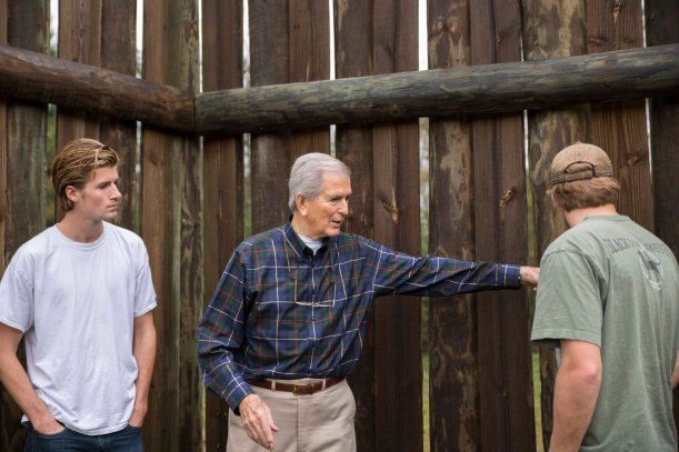 Forrest David Mathews (center), grandson of David Chapman Mathews who originally preserved the site, shows details of the recreated fort wall to his grandsons.